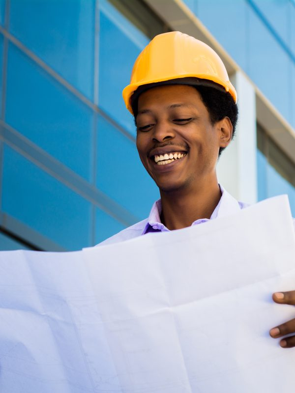 Portrait of Businessman engineer developer holding blueprint working outdoors.
